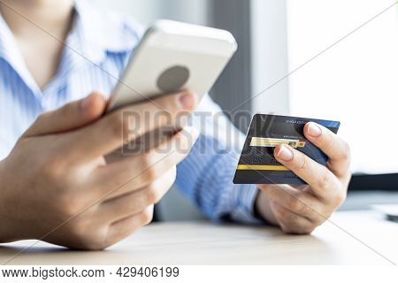Woman Typing On A Laptop Keyboard And Holding A Credit Card, She Fills In Her Credit Card Informatio