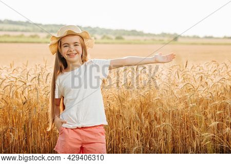 Portrait Of Smiling Kid With Hat Standing In Wheat Field With His Arms Outstretched. Looking At Came