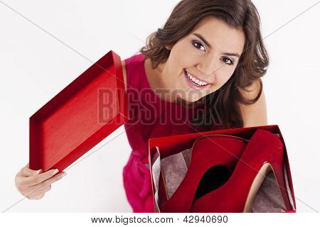 Young woman opening a shoes box