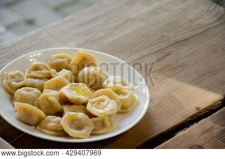 Plate With Dumplings Stands On Wooden Table. Rural Still Life. Homemade Ravioli Served In White Plat