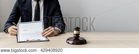 A Male Lawyer Is Signing A Plea Agreement With A Client In A Fraud Case, In Which The Client Has Fil