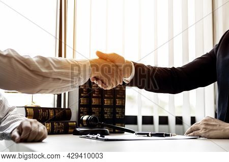 Lawyer And Client Shake Hands, Sign A Lawsuit For The Client, In Which The Client Has Filed A Lawsui