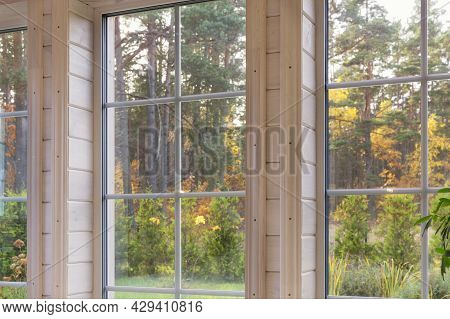 Bright Interior Of The Room In Wooden House With A Large Window Overlooking The Autumn Courtyard. Go