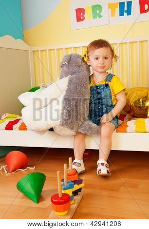 Girl Sitting In The Baby Bed With Boys