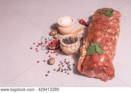 A Piece Of Raw Pork Loin, Marinated Fresh Meat Tied With Culinary Twine With Spices