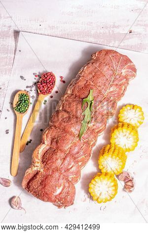 A Piece Of Raw Pork Loin, Marinated Fresh Meat Tied With Culinary Twine, Sweet Corn And Spices