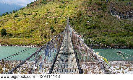 The Longest Suspension Bridge In Himalaya Near The Town Of Punakha In The Himalaya Of Bhutan. Known