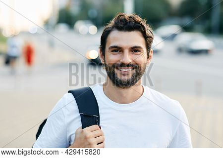 Portrait Of A Handsome Man With A White Toothy Smile On A City Street Holding A Backpack