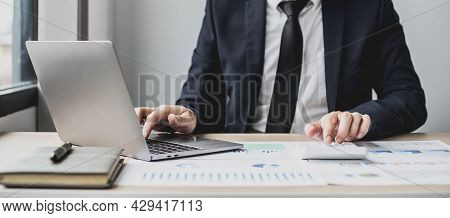 Man Using Laptop And Pressing Calculator, Business Man Sitting In Private Office At His Company, He