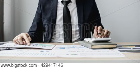 A Man Presses A White Calculator To Calculate Numbers On A Document, A Businessman Is Sitting In His