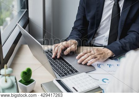 Man In Suit Sitting At Work And Using A Laptop, He Is A Young Businessman Who Founded A Startup, He