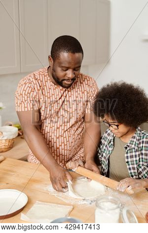 Cute boy rolling dough for homemade pastry while helping his father in the kitchen