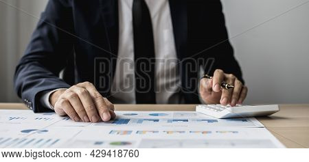 A Businessman Is Reviewing Information From Finance Documents To Bring To Department And Partnership