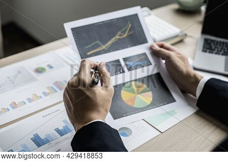 A Businessman Using A Pen To Point A Pie Chart On A Document, He Is Reviewing Financial Documents Fr