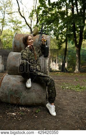 Warrior with paintball gun poses on rusty barrels