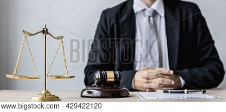 A Male Lawyer Sits In His Office, On A Table With A Small Hammer To Beat The Judge's Desk In Court.
