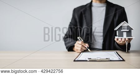 A Saleswoman Checks The Lease And Holds A Small Gray Model Of House And House Keys In Preparation Fo