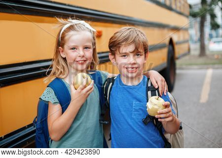 Children Boy And Girl Students Friends Eating Apples Healthy Snack By Yellow School Bus Outdoors. Ed