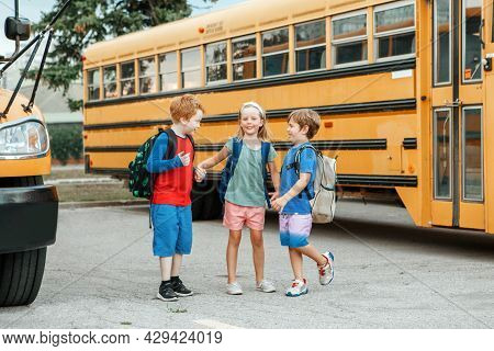 Children Boys And Girl Kids Students Standing And Talking Near Yellow School Bus. Friends Schoolmate