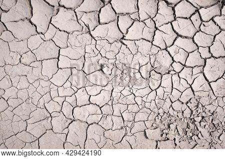 Area Of Dried Land Suffering From Drought, Ground Cracks. Texture Of Grungy Dry Cracking Parched Ear