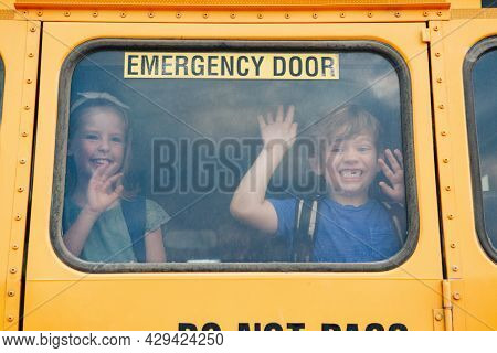 Funny Happy Smiling Boy And Girl Kids Students Looking Out Of School Yellow Bus Window. Waving Sayin