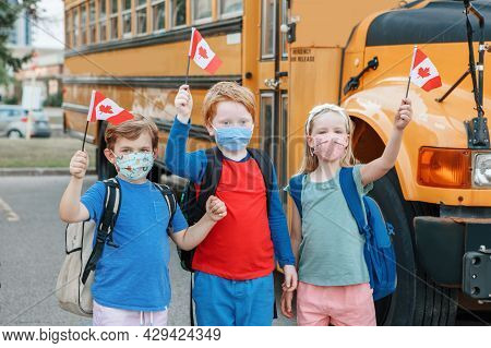 Proud Happy Students Children With Face Masks Holding Canadian Flags. Education And Back To School O