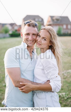 Middle Age Caucasian Man And Young Woman Hugging In Park Outdoor. Happy Romantic Couple In Love Dati