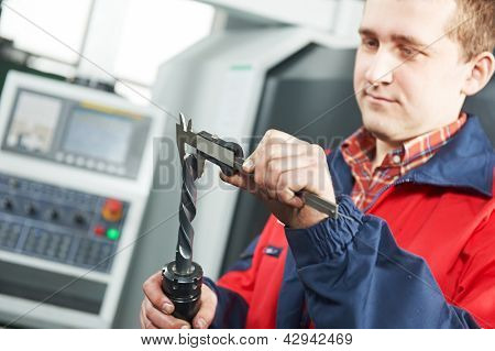 mechanical technician worker measuring detail tool befor processing on cutting machine center at workshop at manufacturing