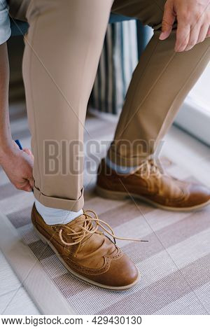 Groom Puts On Brown Brogues On His Legs. Close-up