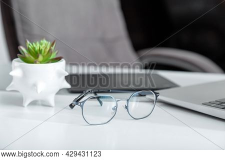 Stylish Blue Male Glasses For Vision On Desktop With Laptop Graphics Tablet And Plant. Fe, Ale Eyegl