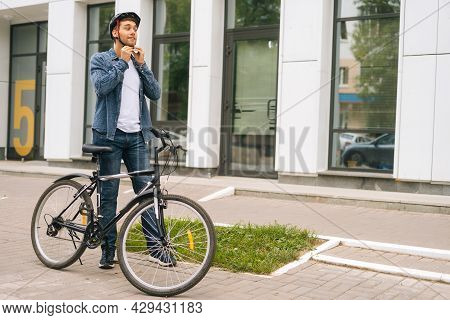 Wide Shot Portrait Of Handsome Young Man Putting Helmet On Head Before Going To Go Ride By Bicycle I