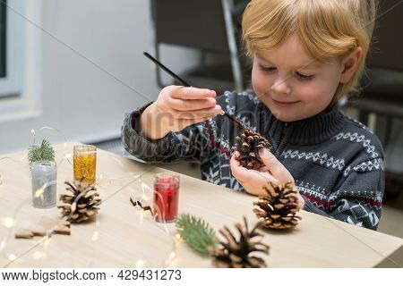 Christmas Kids Craft Activities At Home. Little Child Painting Pine Cones And Wooden Christmas Tree