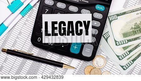 On The Desktop Are Reports, A Pen, Cash, A Calculator And A Card With The Text Legacy. Business Conc