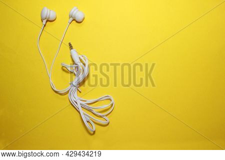 Flat Lay Concept: Headphones On A Yellow Background. White Headphones On A Yellow Background, Top Vi