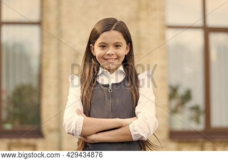 Believe In Yourself. Confident Child Keep Arms Crossed Outdoors. Confident Look Of Little Pupil. Bac