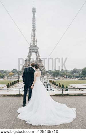 Bride And Groom Having A Romantic Marriage In Paris. Wedding Couple On A Background Of Eiffel Tower
