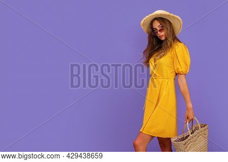 Beautiful Young Woman In White Dress, Summer Straw Hat, Sunglasses, Straw Bag Isolated On Pastel Vio