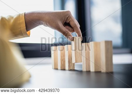 Businesswoman Picking Up A Block Of Wood From A Row, Solving Problems That Arise During Planned Busi
