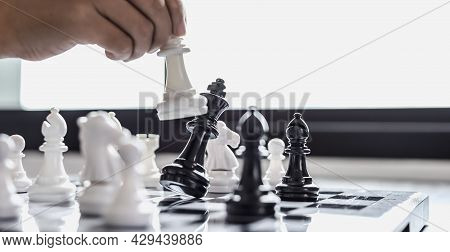 Close-up A Businesswoman Holding A White Chess Piece And Colliding With Black Chess Until She Almost
