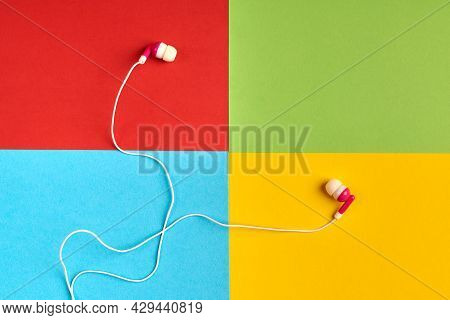 Earphones On Colorful Background Of Famous Computer Corporation, Software Manufacturer Logo. Audio S