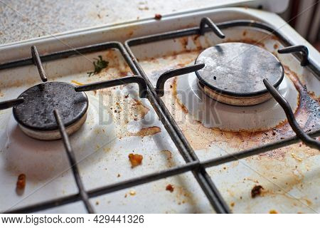 Dirty Stove With Food Leftovers. Unclean Gas Kitchen Cooktop With Greasy Spots, Old Fat Stains, Fry