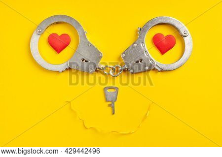 Handcuffs Smile Shape On Yellow Background. Freedom Concept. Imprisonment, Deprivation Of Liberty An