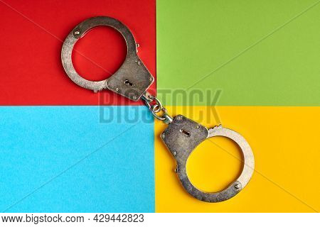 Handcuffs On Paper In Colors Of Famous Computer Corporation, Cyber Criminal Caught Concept. Software