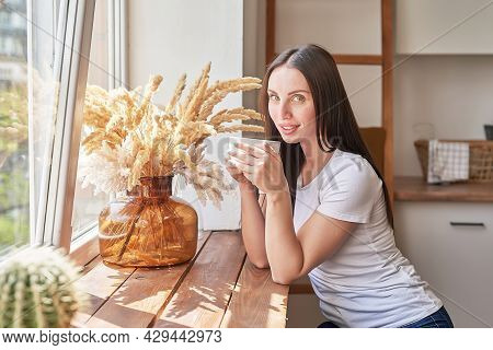 Young Woman With Cup Of Coffee Or Tea At Window In Coffee Shop. Good Morning Concept. Cozy Breakfast