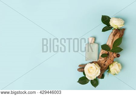 Perfume In Glass Bottle With Blossom Flowers Roses And Wood On Blue Background, Copy Space
