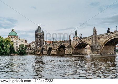 Charles Bridge,tourist Boat On Vltava River,prague, Czech Republic. Buildings And Landmarks Of Old T