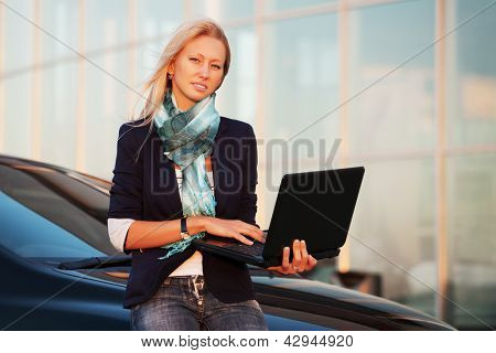 Young businesswoman with laptop against office windows