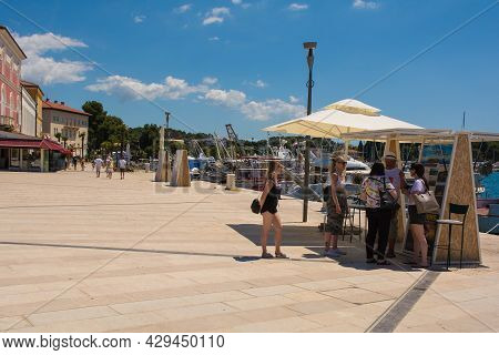 Porec, Croatia- July 10th 2021. A Day Trip Vendor On The Seafront Tries To Sell A Boat Trip To Four