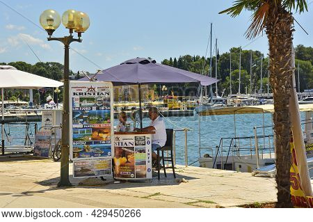 Porec, Croatia- July 10th 2021. A Day Trip Vendor Selling Boat Trips At The Seafront Waits For Passi