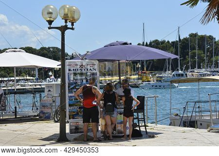 Porec, Croatia- July 10th 2021. A Day Trip Vendor On The Seafront Tries To Sell A Boat Trip To Three